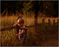 Child Portrait of Little boy in overalls at sunset by fence